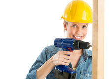 Construction Worker Using Power Drill On Wooden Plank. Portrait of beautiful construction worker using power drill on wooden plank isolated over white background Royalty Free Stock Image