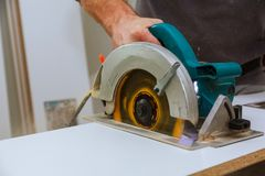 Construction worker using slider compound mitre saw or circular saw for cutting massive wood board. Details of construction, renovation works Royalty Free Stock Photos