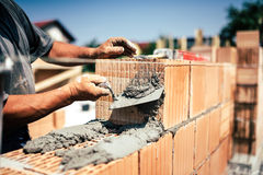 Construction worker using spatula and trowel for building walls with bricks and mortar Royalty Free Stock Photos
