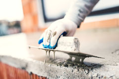Construction worker using steel trowel for plastering Stock Photos