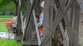 Construction worker using tablet PC and looking through scaffolding. In summer day stock video