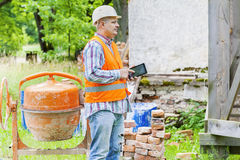 Construction worker using tablet PC near concrete mixer Royalty Free Stock Photos