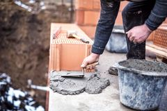 Construction worker using trowel and cement for installing the brickwork Stock Photography