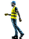 Construction worker walking  safety vest silhouette. One construction worker walking with safety vest silhouette isolated in white background Royalty Free Stock Image