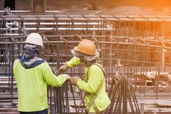 Construction worker Wearing green safety shirt Help each other use mild steel. Bind the big steel bars together. In the area that. Is building a large building royalty free stock images