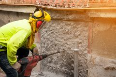 Construction worker Wearing green safety shirt Is using a large drill machine to drill a wall in the area that is building a large. Building royalty free stock photo