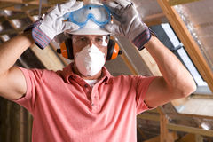 Construction worker wearing protective mask in attic Stock Images