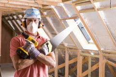 Construction worker wearing protective mask and holding tools in attic Royalty Free Stock Image