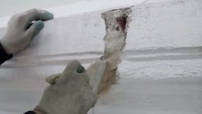 Worker wearing protective gloves sweeps dust with paint brush from crack in wall. Construction worker wearing protective white gloves sweeps out dust by using stock video footage
