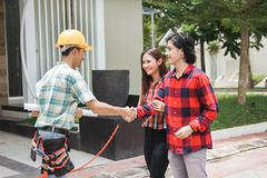 Construction worker welcoming the house owner. Portrait of construction worker welcoming the house owner. shaking hand. buy new house concept Royalty Free Stock Photo