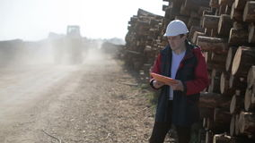 Construction worker in white helmet is standing on the road next to the logs and monitoring freight transport. Truck with tractor on the board quickly moves stock footage