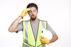 Construction worker wipes the sweat of his forehead in a gesture Royalty Free Stock Photography