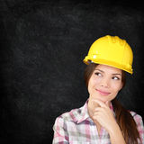 Construction worker woman on chalkboard texture. Woman architect, engineer, surveyor or construction worker wearing protection hardhat thinking looking Stock Photos