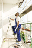 Construction worker in work attire and protective gloves enters a ladder with a drill in hand. Royalty Free Stock Photos