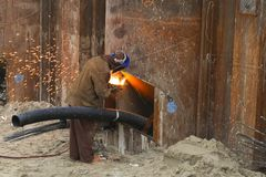 Construction Worker at work and repairing some steel pipes. Wearing a mask Stock Photos