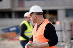 Construction worker at work on construction site. Using an electronic device. Outdoors Royalty Free Stock Photography