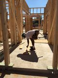 Construction worker working on the framing process for a new a house Stock Photos