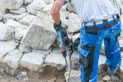 Construction worker is working with granite stones royalty free stock image