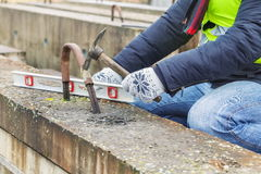 Construction worker working with hammer near concrete blocks. In winter day Stock Photography