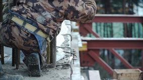 Construction worker working on a construction site. Clip. Employee works at the construction site.  Stock Images