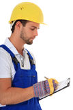 Construction worker writing on clipboard. Portrait of a construction worker writing on clipboard. All on white background Stock Photo