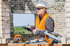 Construction worker writing near tools in unfinished building Royalty Free Stock Photography