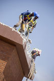 Construction Workers. From below hard at work. Image Tilted royalty free stock photography