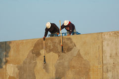 Construction workers. Cleaning cement wall Stock Photos
