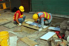 Construction Workers. Construction engineers working on reconstruction of sidewalk Royalty Free Stock Photo
