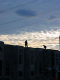 Construction workers 3. 2 construction workers finishing day's work on the top of half build townhome complex, beautiful sunset in the background Royalty Free Stock Photo