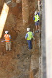Construction workers. Three construction workers, one holding blueprints, on an excavation site Royalty Free Stock Photography