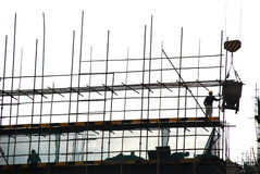 Construction workers. Busily woriking on the scaffold,silhouette royalty free stock photo
