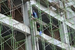 Construction Workers at Altitude. 20/12/2017, Yogyakarta, Indonesia: Workers working on new building construction at altitude with minimal safety standards Stock Photography