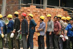 Construction Workers in Beijing. Construction workers in line for food during a lunch break in Beijing China Stock Photos
