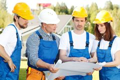 Construction workers with blueprint. Teamwork concept royalty free stock photography
