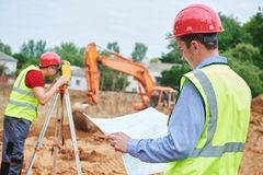 Construction workers on building area. Foreman with blueprint and surveyoor. With theodolite stock photography