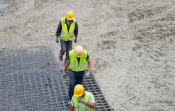 Construction workers carrying armature Royalty Free Stock Photo