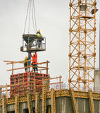 Construction workers casting concrete lowered from a crane Stock Images