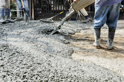 Construction Workers Cementing Road. Men pouring fresh concrete mix on road Royalty Free Stock Photography