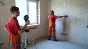 Construction workers check length with measure tape and laser tool. On building site. Workers control red beam level accuracy on concrete wall. Safety policy stock video footage