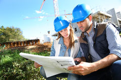 Construction workers checking the blueprint Stock Photography