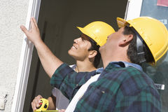 Construction Workers Checking Window. Two construction workers checking window at construction site stock image