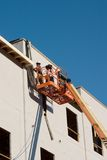 Construction Workers On A Cherry Picker. Two construction workers on a cherry picker working on a building under construction. Worker faces are hidden and not royalty free stock photography