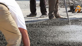 Construction workers compacting liquid cement into a runway construction stock video