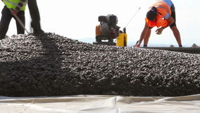 Construction workers compacting liquid cement into a runway construction stock video footage