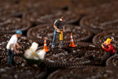 Construction Workers in Conceptual Imagery With Cookies. Miniature Construction Workers in Conceptual Imagery With Cookies Stock Photography