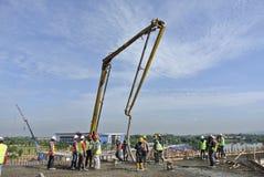 Construction workers with concrete pump crane Stock Photos