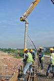 Construction workers with concrete pump crane Stock Image