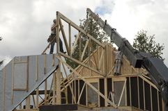 Construction workers and crane 1. Workers framing a roof of a new house with the help of a construction crane stock photography
