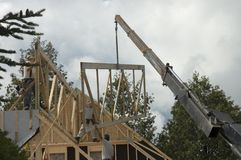 Construction workers and crane 2. Workers framing a roof of a new house with the help of a construction crane royalty free stock photography